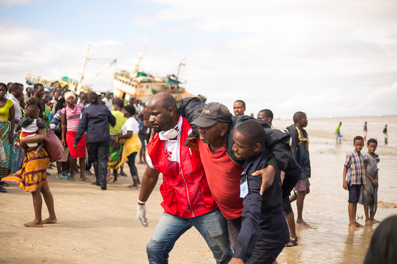21 March 2019, Beira port, Mozambique Survivors of Cyclone Idai, cut off by flood water, arrive by rescue boat to an evacuation centre in Beira.  Volunteers from the Mozambique Red Cross are providing first aid, medical triage, emergency supplies like blankets and helping with the registration of evacuees.  Cyclone Idai made landfall on the evening of 14/15 March near the central Mozambican city of Beira. The cyclone – with maximum sustained winds estimated as between 170 and 190 km/h – brought torrential rains to Sofala, Zambezia, Manica and Inhambane provinces. Thousands of homes were flattened by the cyclone and flooding continues as heavy rainfall over neighbouring Malawi and Zimbabwe is causing rivers in Mozambique to burst their banks. Large areas close to Buzi and Pungwe rivers have been severely flooded, up to several metres in some parts. Flood survivors have sought refuge in trees and on the roofs of building still standing. The cyclone caused significant destruction in Beira – Mozambique's fourth largest city with a population of over 500,000 - and surrounding villages.